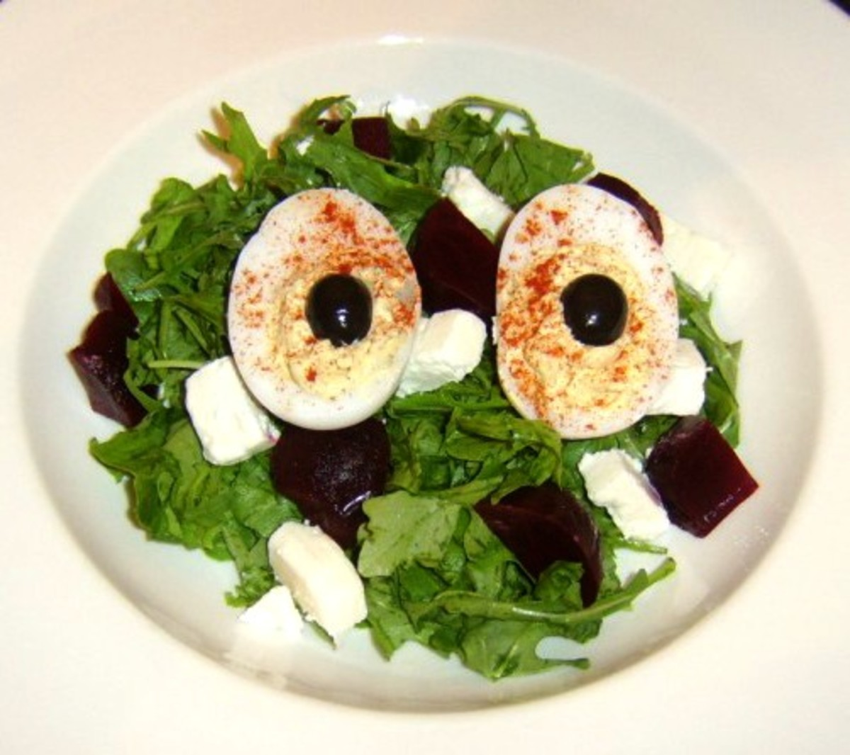 Deviled duck egg is served on a bed of green leaves, beetroot and Greek feta cheese