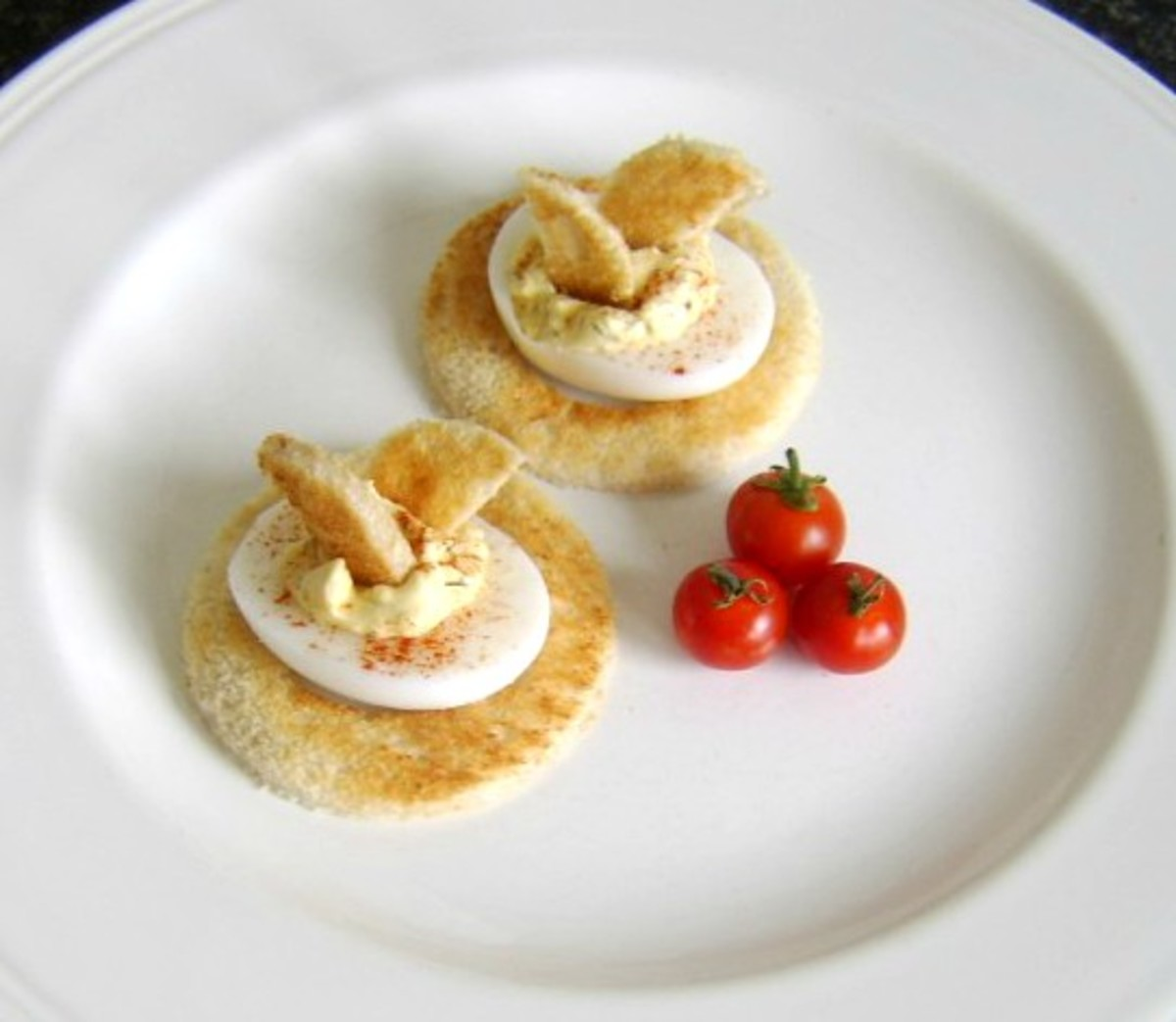 Basic deviled duck eggs are served on circles of toast and garnished with cherry tomatoes