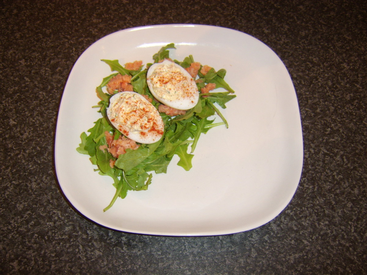 Smoked salmon deviled duck eggs are laid on the salad bed