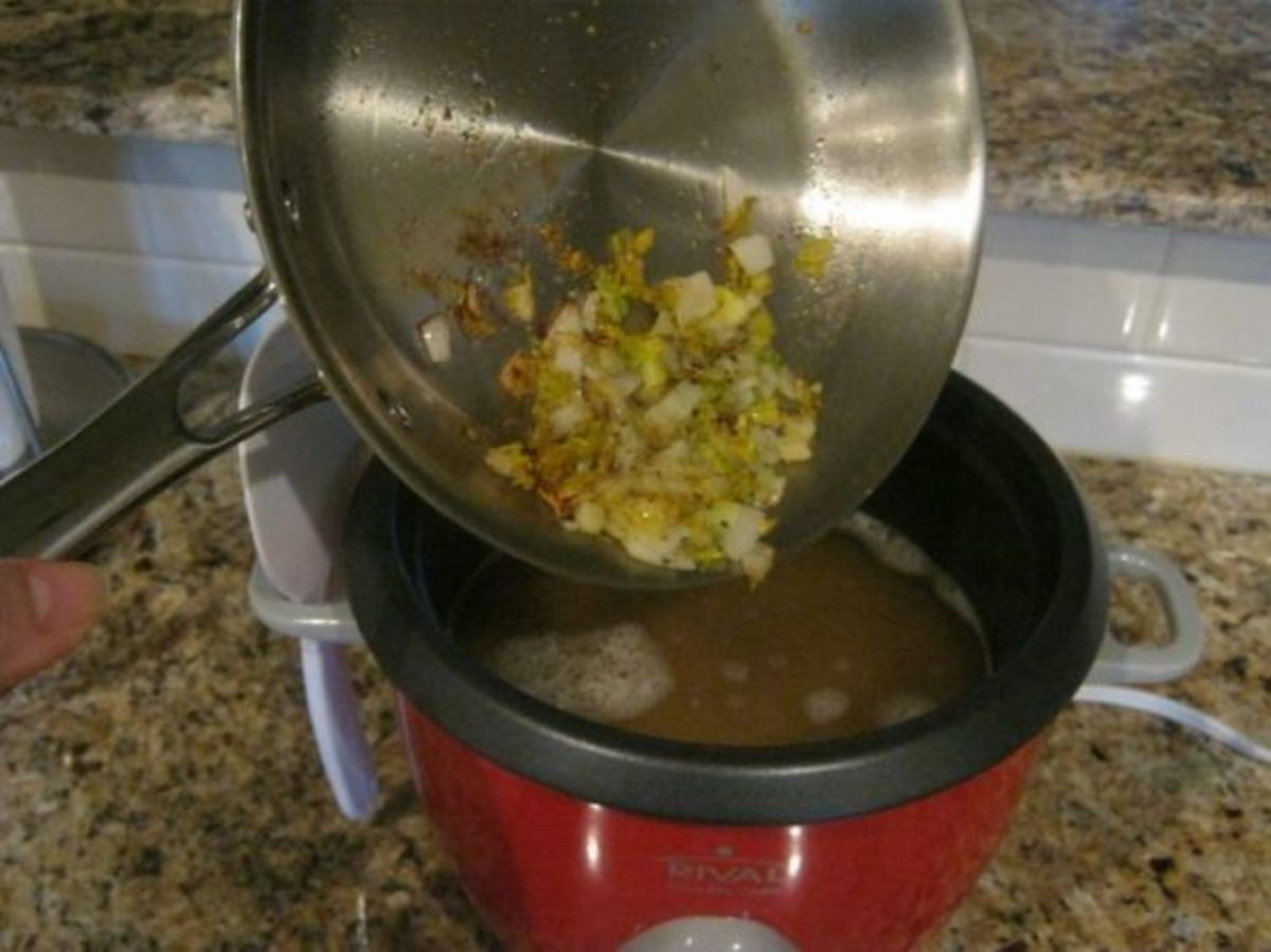 Stir the browned vegetables and spices into the rice as it cooks in the rice cooker.