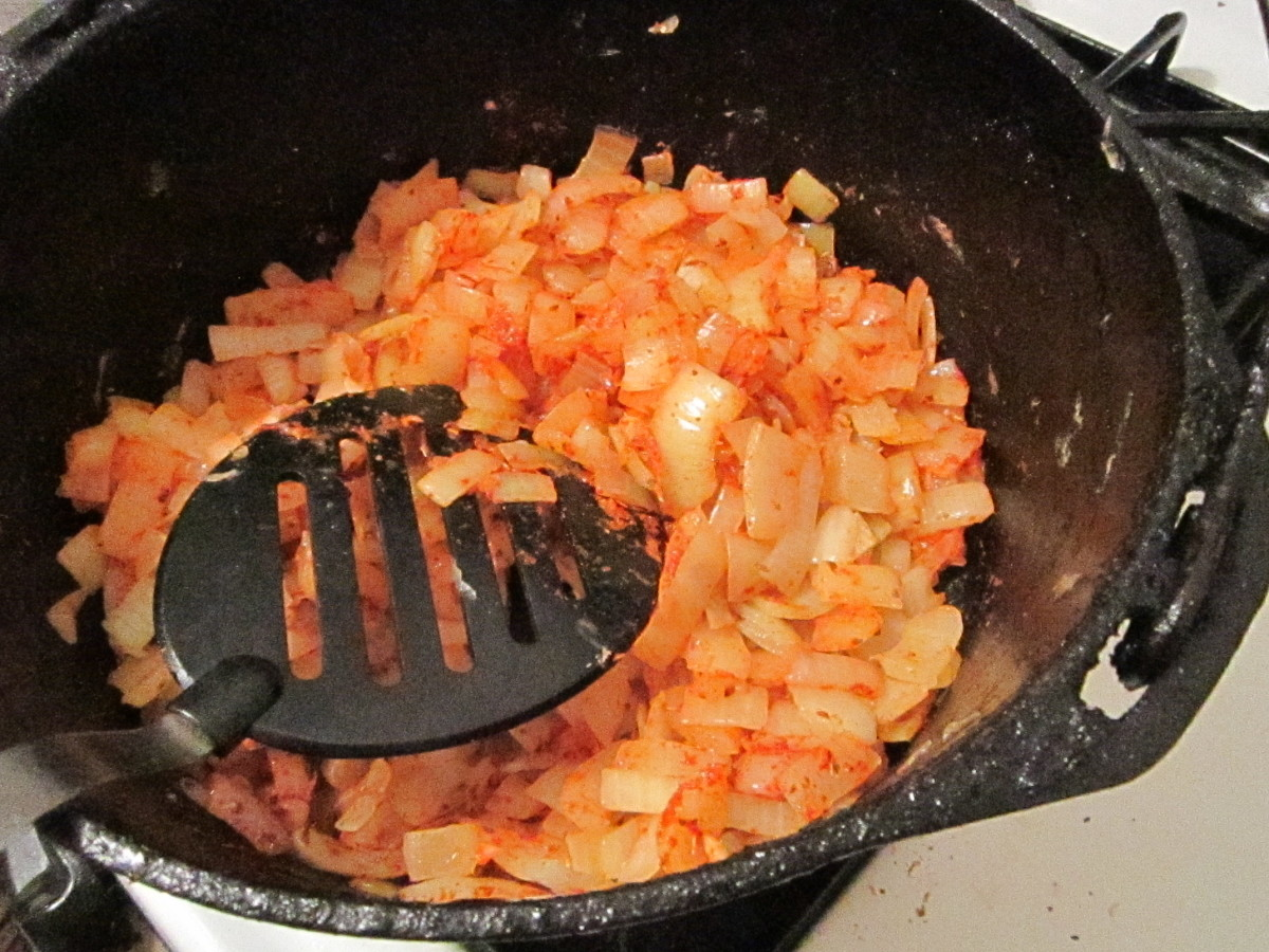 Sauteing and stirring the Mixture of Seasonings with the Onions.