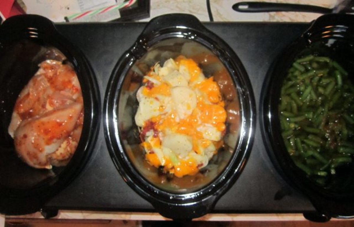 Three dishes ready to go: marinated chicken, loaded potatoes, and green beans.