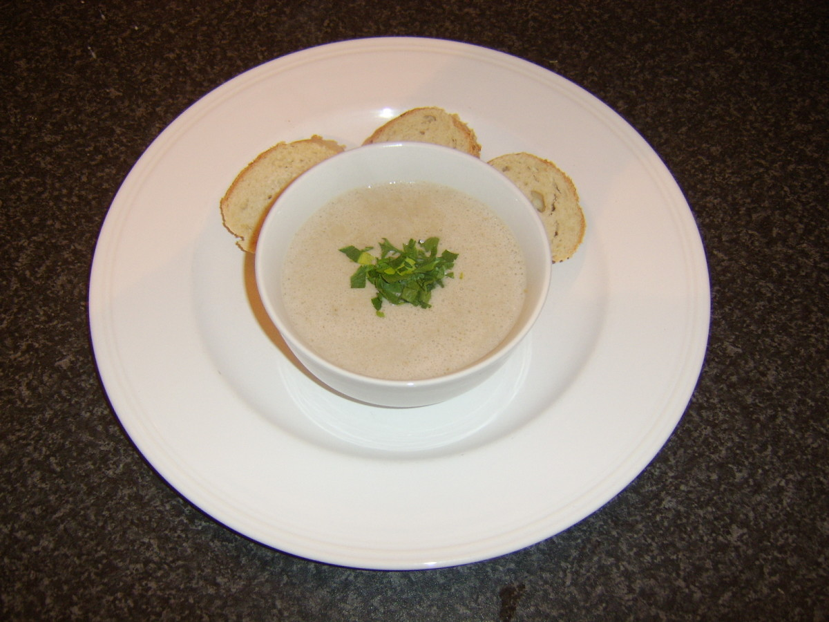 Cream of chestnut and roast duck soup is served garnished with a little parsley and with some crusty bread on the side