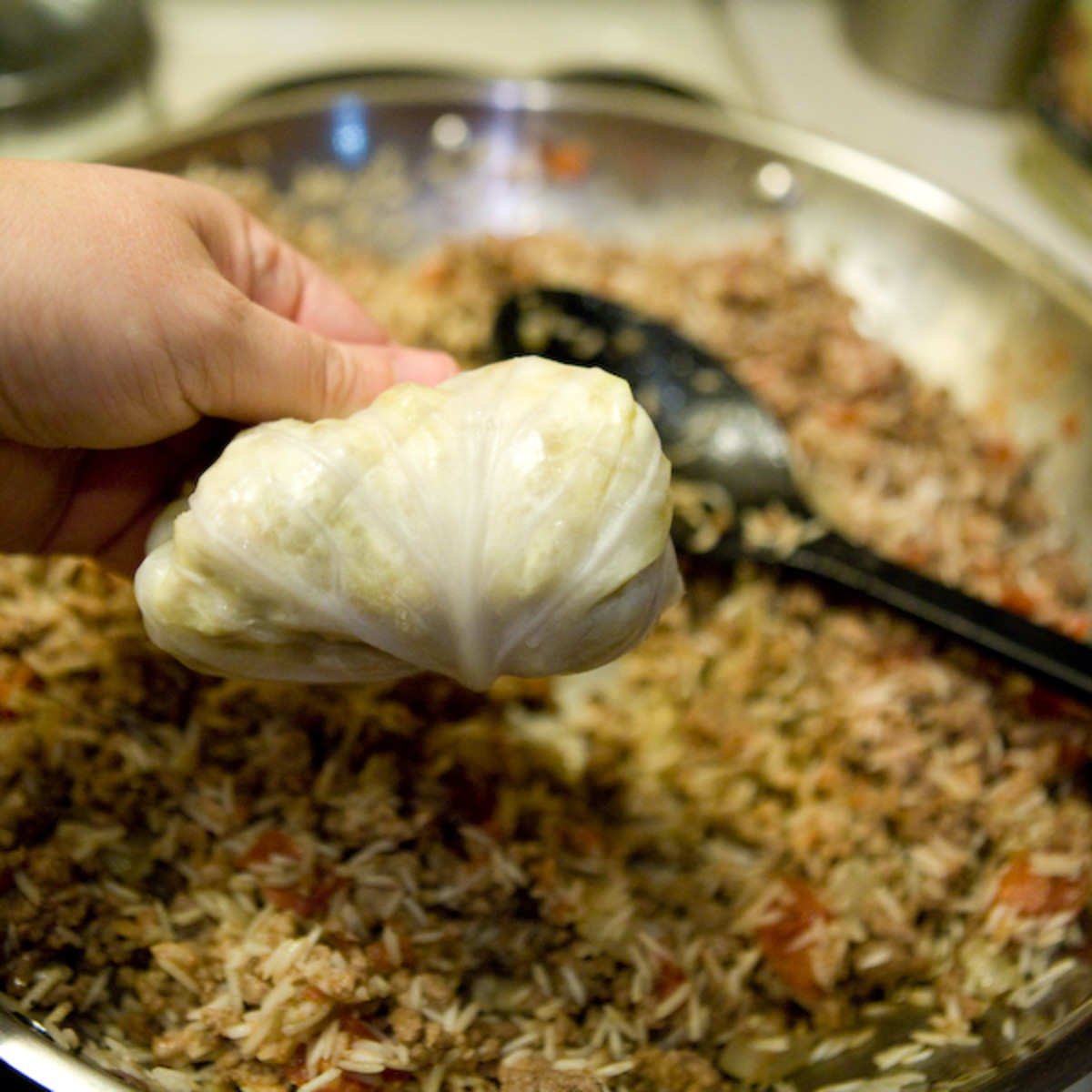 Place a spoonful of meat and rice mixture into a cabbage leaf and roll.