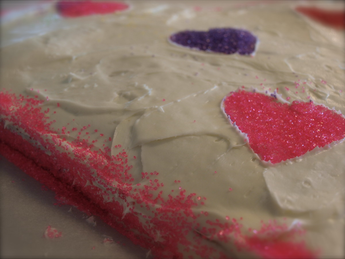 Using decorations of your choice, decorate the cake.  To get the glitter hearts, I used a heart-shaped cookie cutter and gently laid it on the cake surface.  Then I added glitter to the center of the cutter.