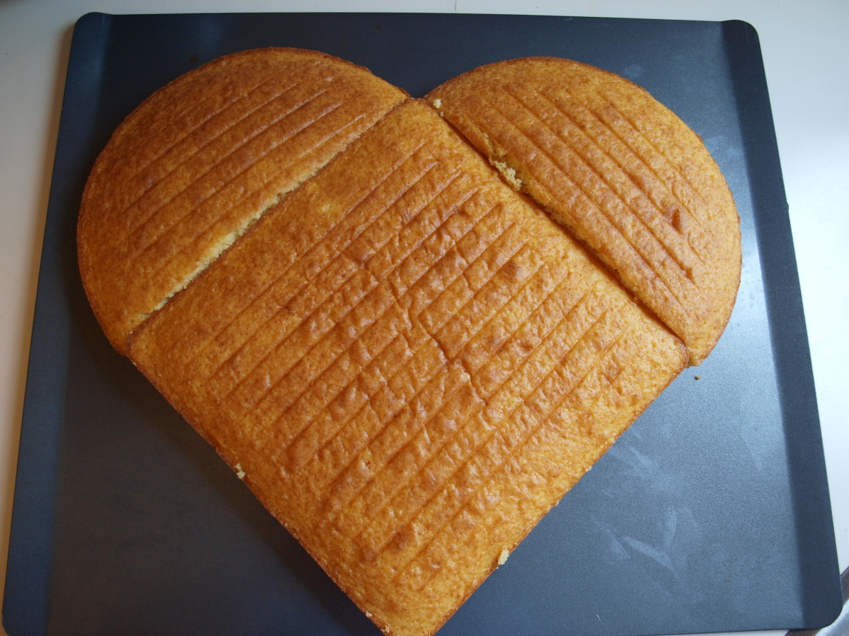 Using a large tray, assemble the unfrosted cake.  Place the square cake on the diagonal and place the two halves of the circular cake at the top left and right.  The heart shape is formed.
