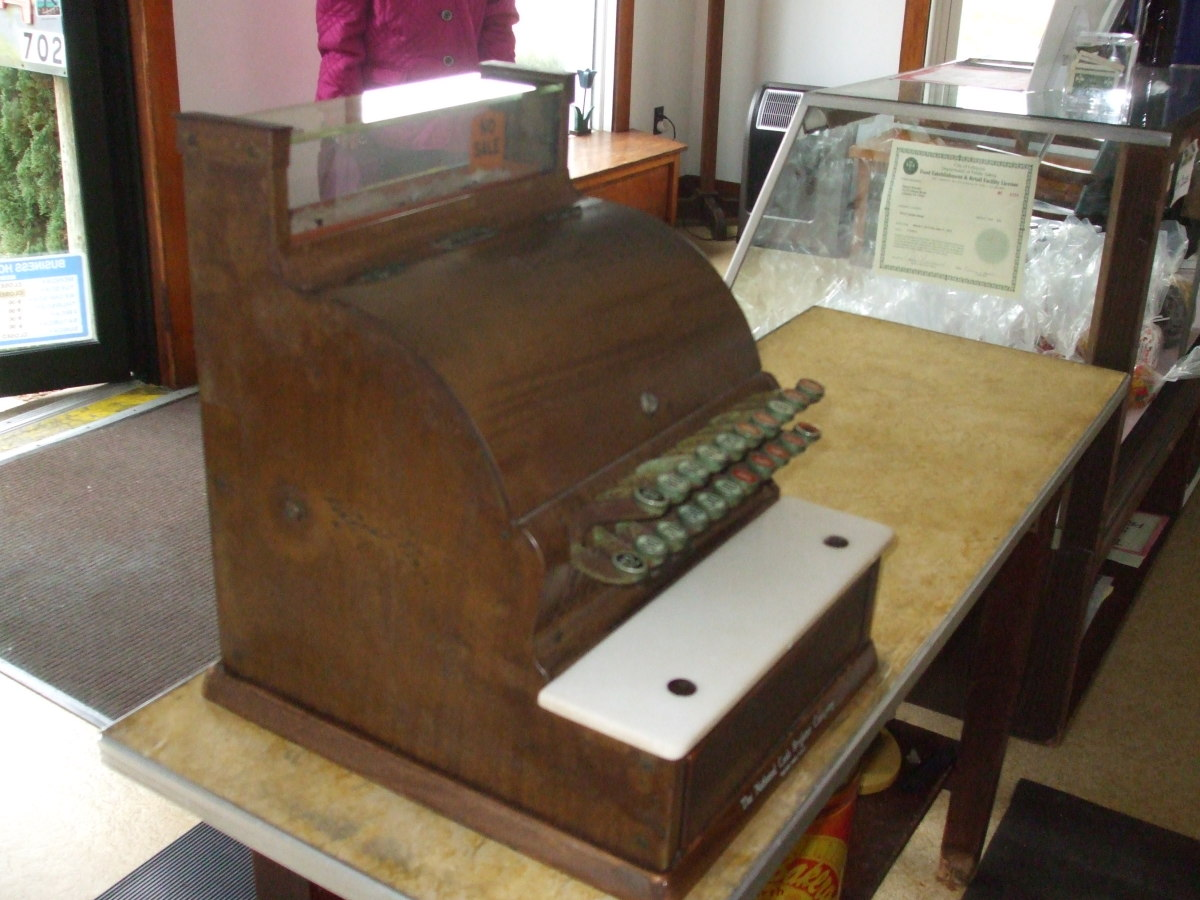 A glass and wood candy case sits next to the cash register.