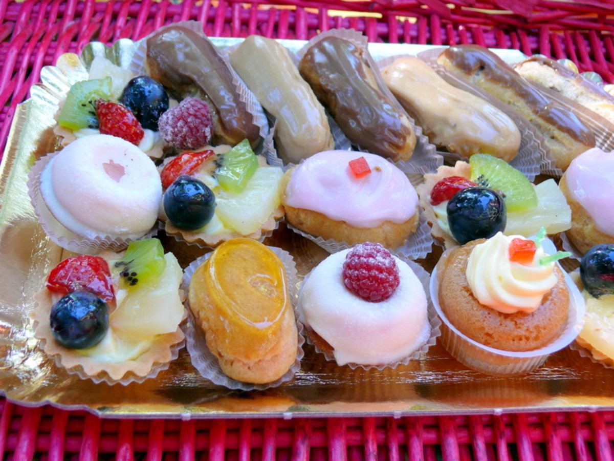 A silver tray of elegant petit fours and miniature tarts, eclairs and puddings
