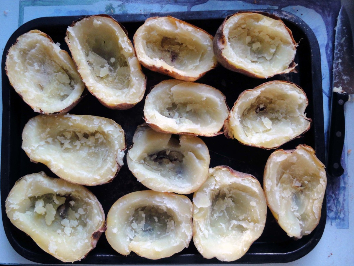 After potatoes are baked, cut in half and scoop out the potatoes to leave the skins.