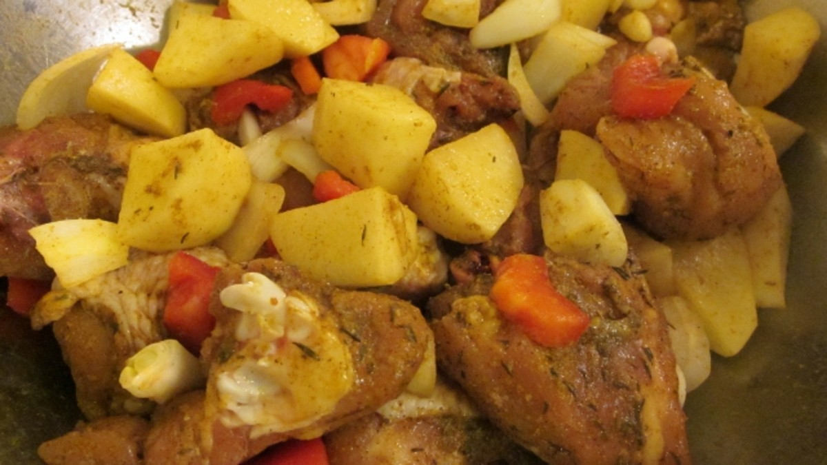 Seasoned, raw chicken leg pieces and potatoes are ready for browning.