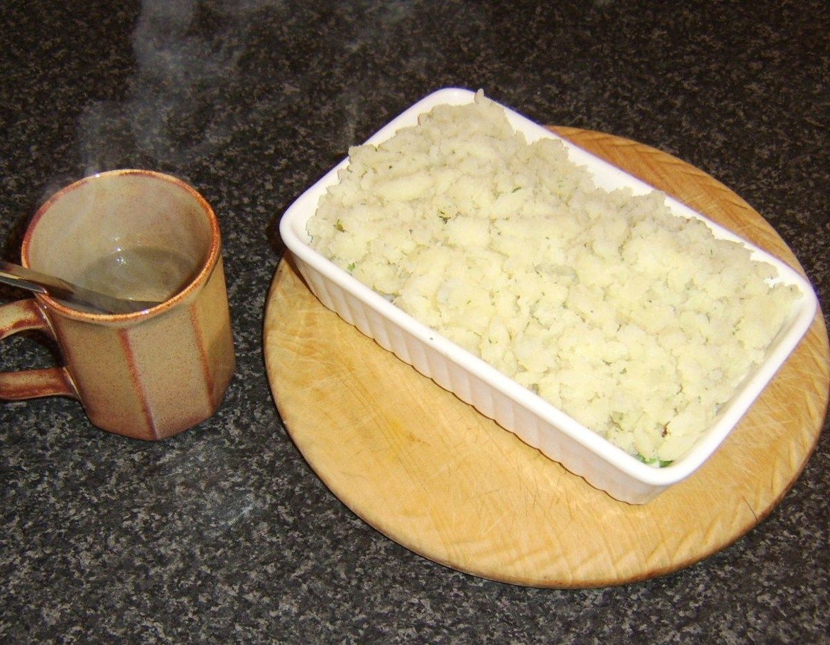Spreading the potato on the fish pie with a hot knife