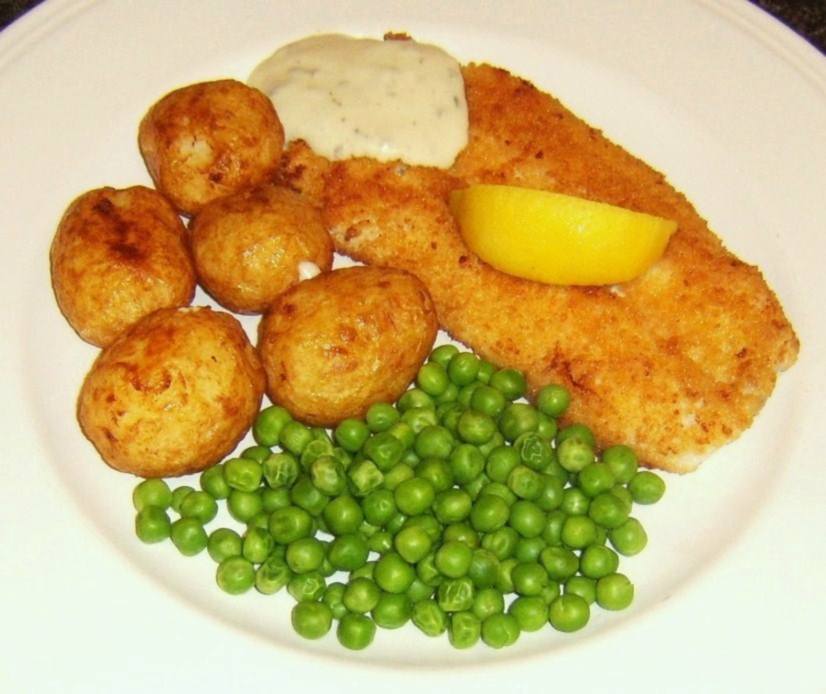 Breaded haddock fillet is shallow fried before being served with roast potatoes, peas and tartare sauce