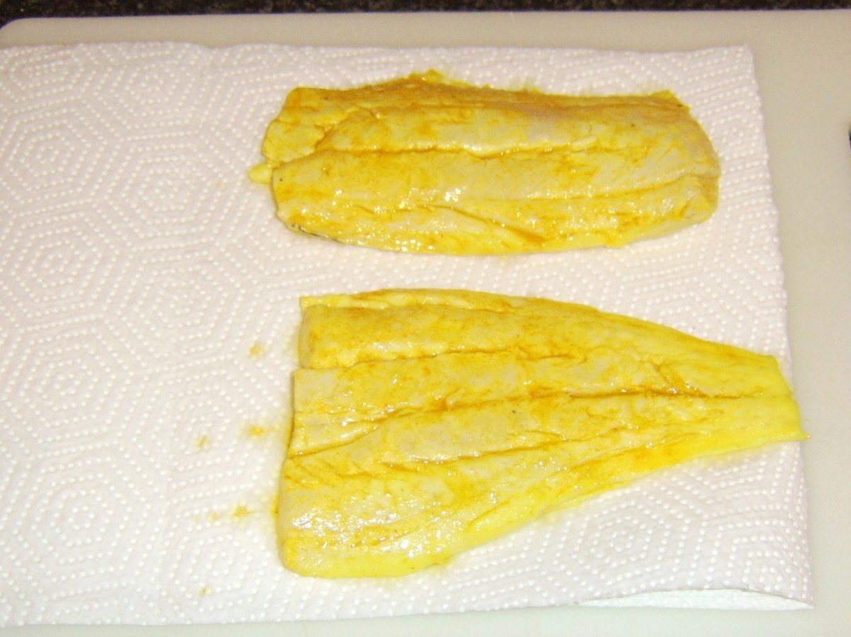 Marinated haddock fillets are patted dry with kitchen paper