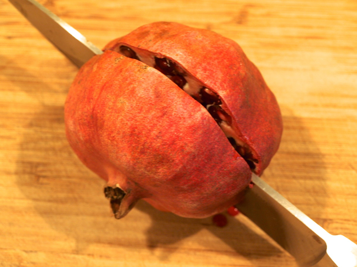 2. Cut the pomegranate in half.