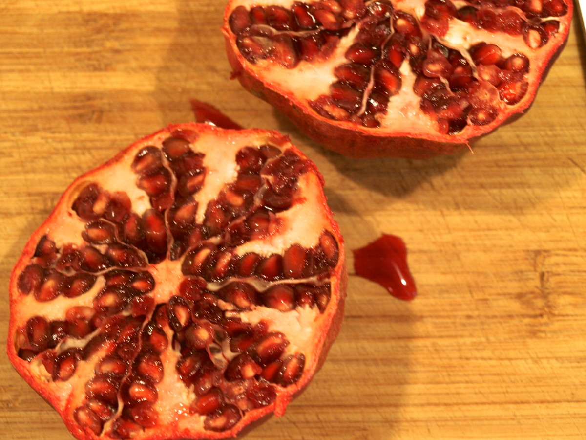 3. Using your thumbs, gently pull of edges pomegranate back. This will loosen the seeds.
