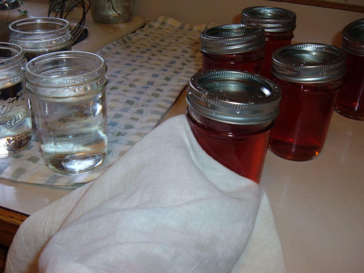Use a towel to protect your hand from the hotness of the jars as you screw the cap on.