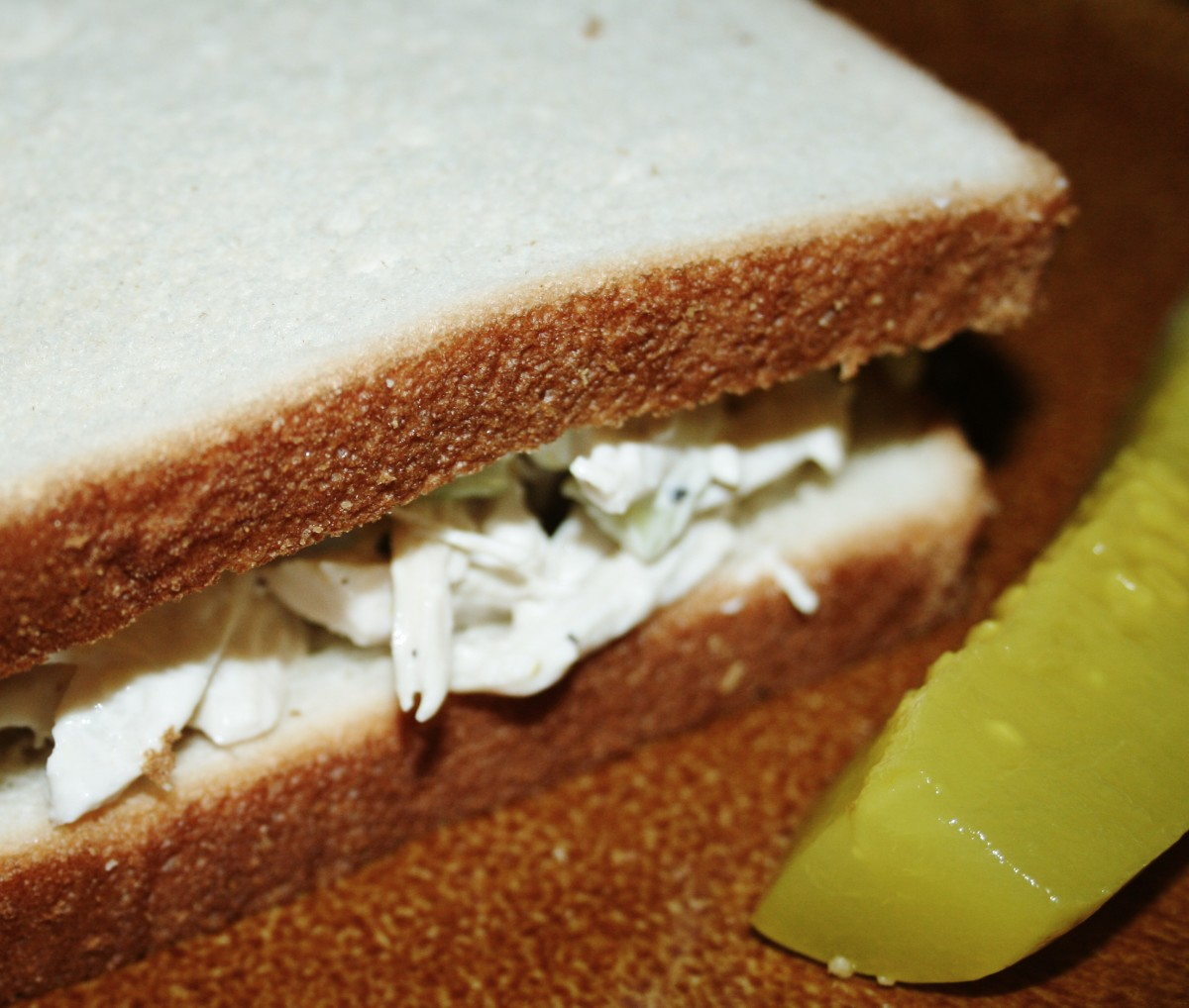 A chicken salad sandwich with pickle on the side, great for lunch!