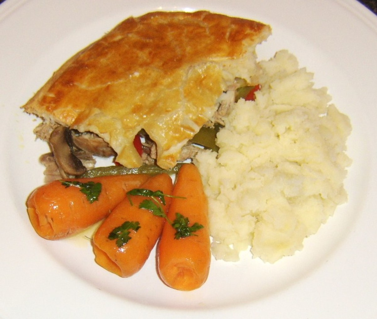 Rabbit and pork pie with bell peppers and mushrooms is served with mashed potatoes and Chantenay carrots