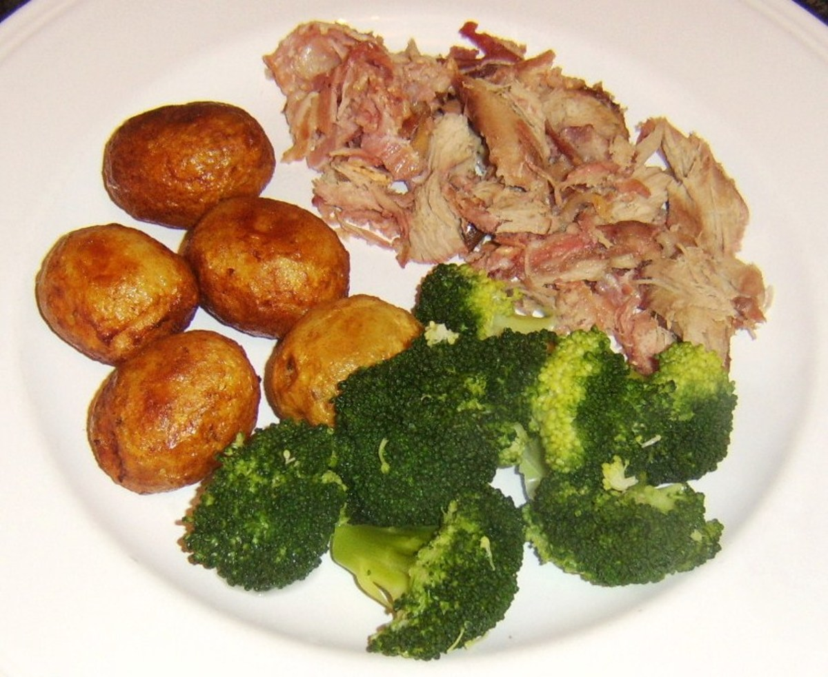 Roast rabbit saddle meat is plated with roast potatoes and broccoli
