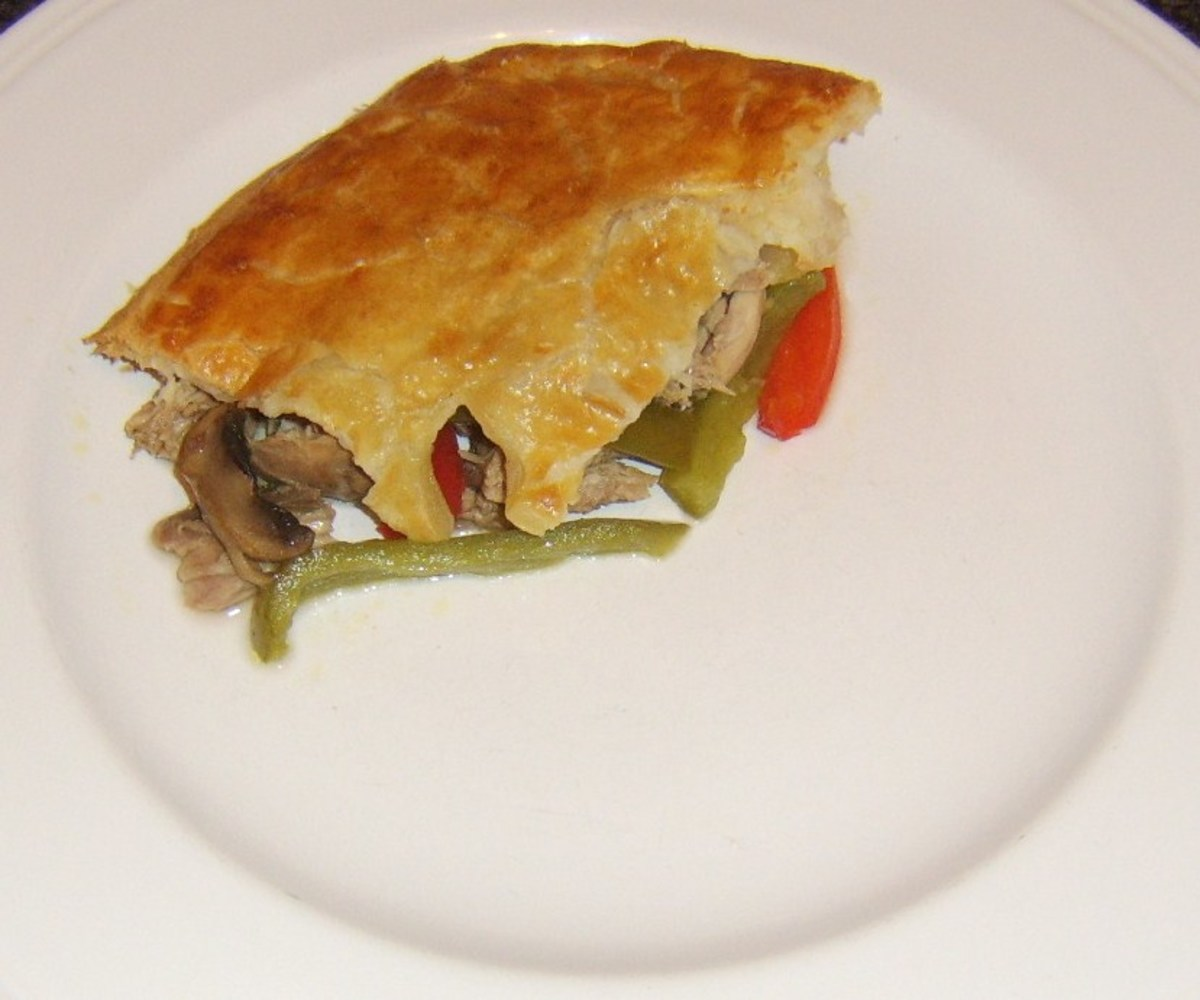 A piece of pastry is laid on top of the rabbit and pork pie filling