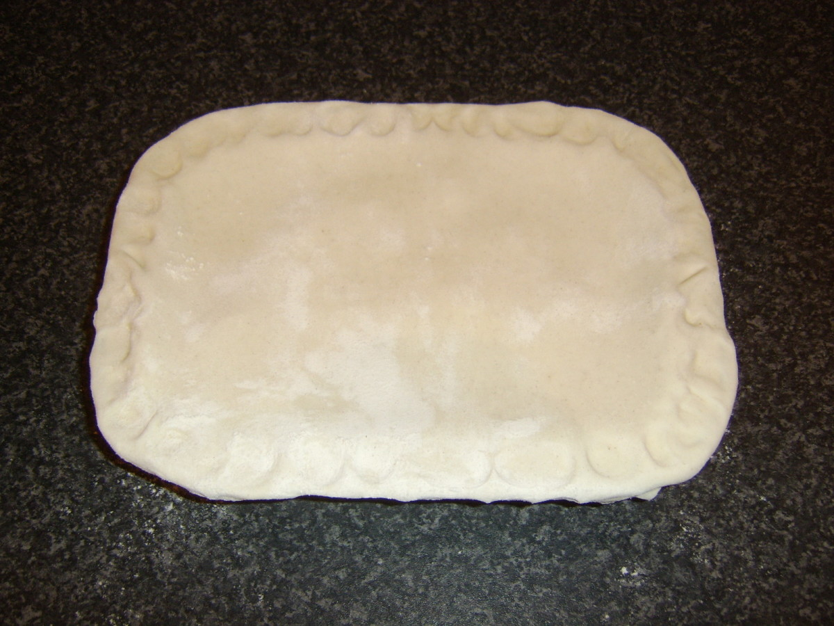 Pastry is fitted and crimped over pie filling