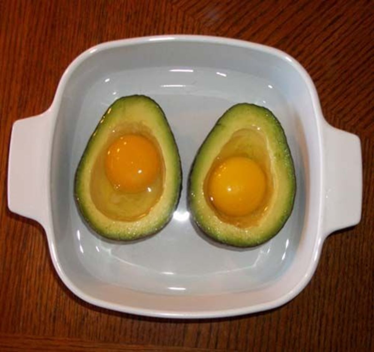 Pour eggs into avocado halves in water bath.