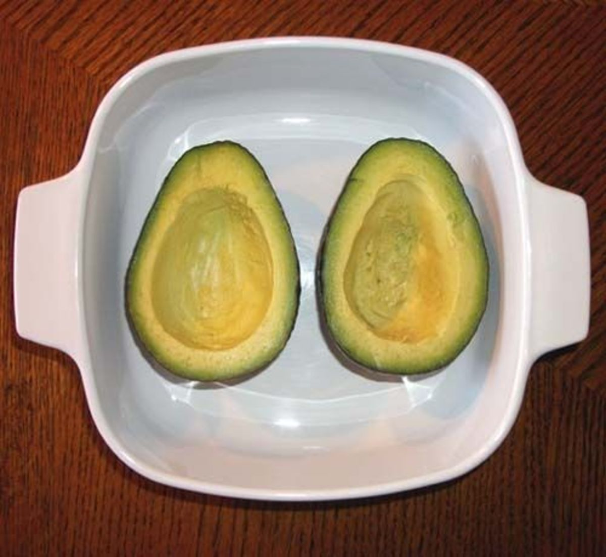 Two avocado halves in a baking dish