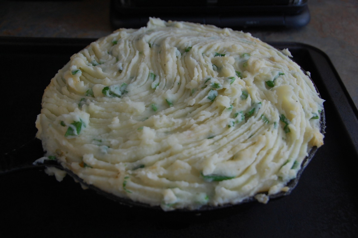 mashed potatoes placed on top in an even layer, and run over with a fork for nicer browning