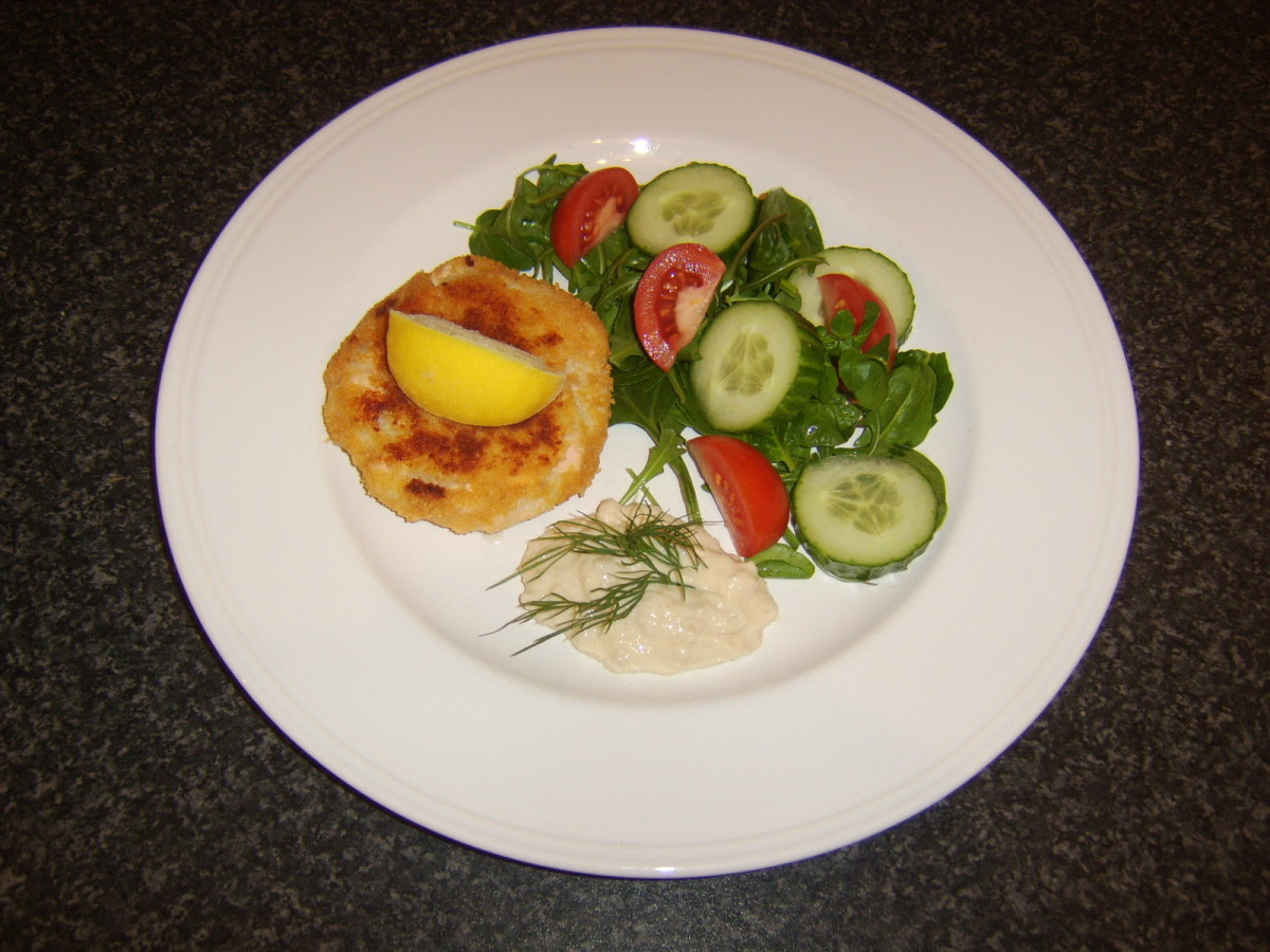 Breaded salmon cake with horseradish sauce and a simple salad