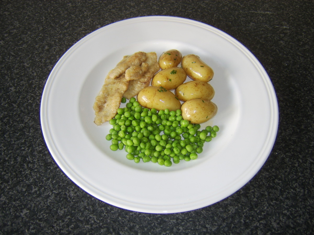 Flounder fillets are fried in butter and served simply with new potatoes and peas