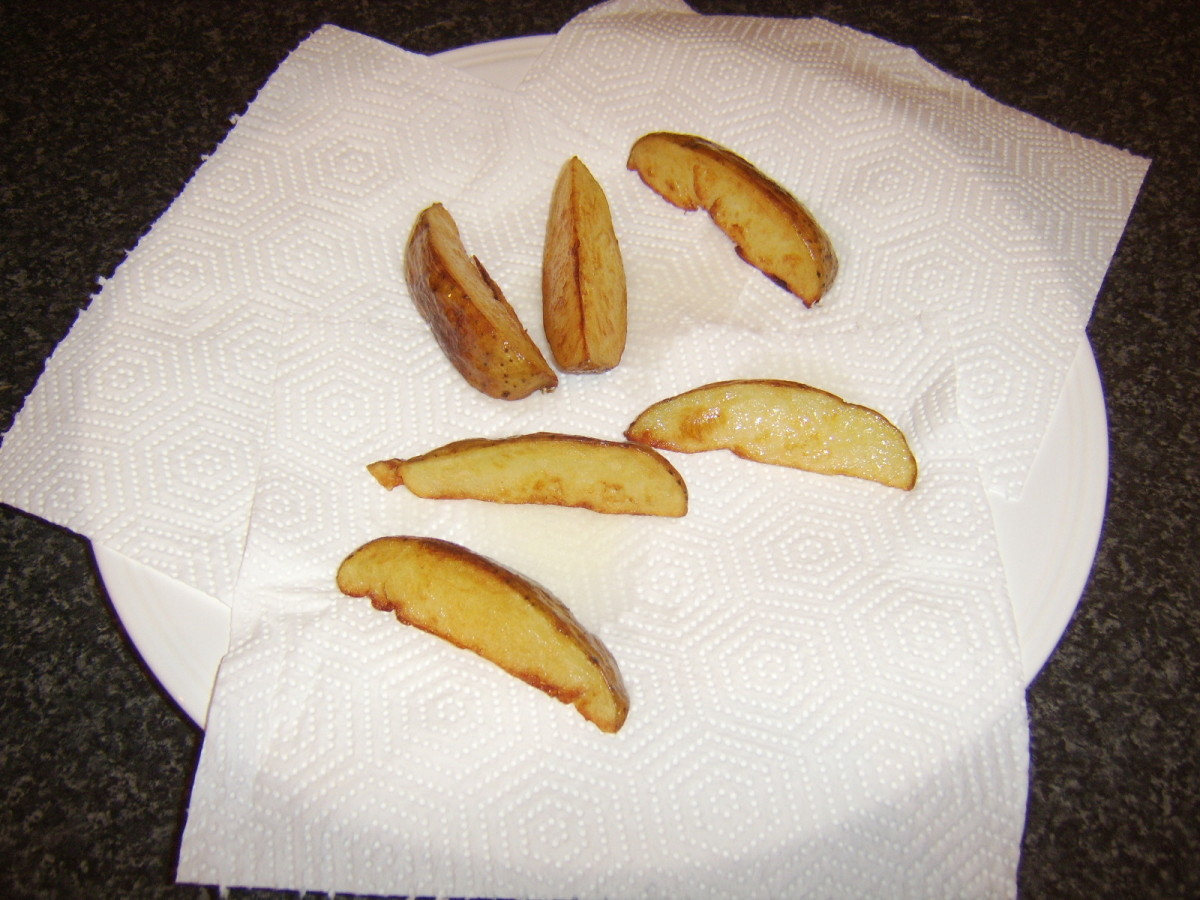 Deep fried potato wedges are drained on kitchen paper