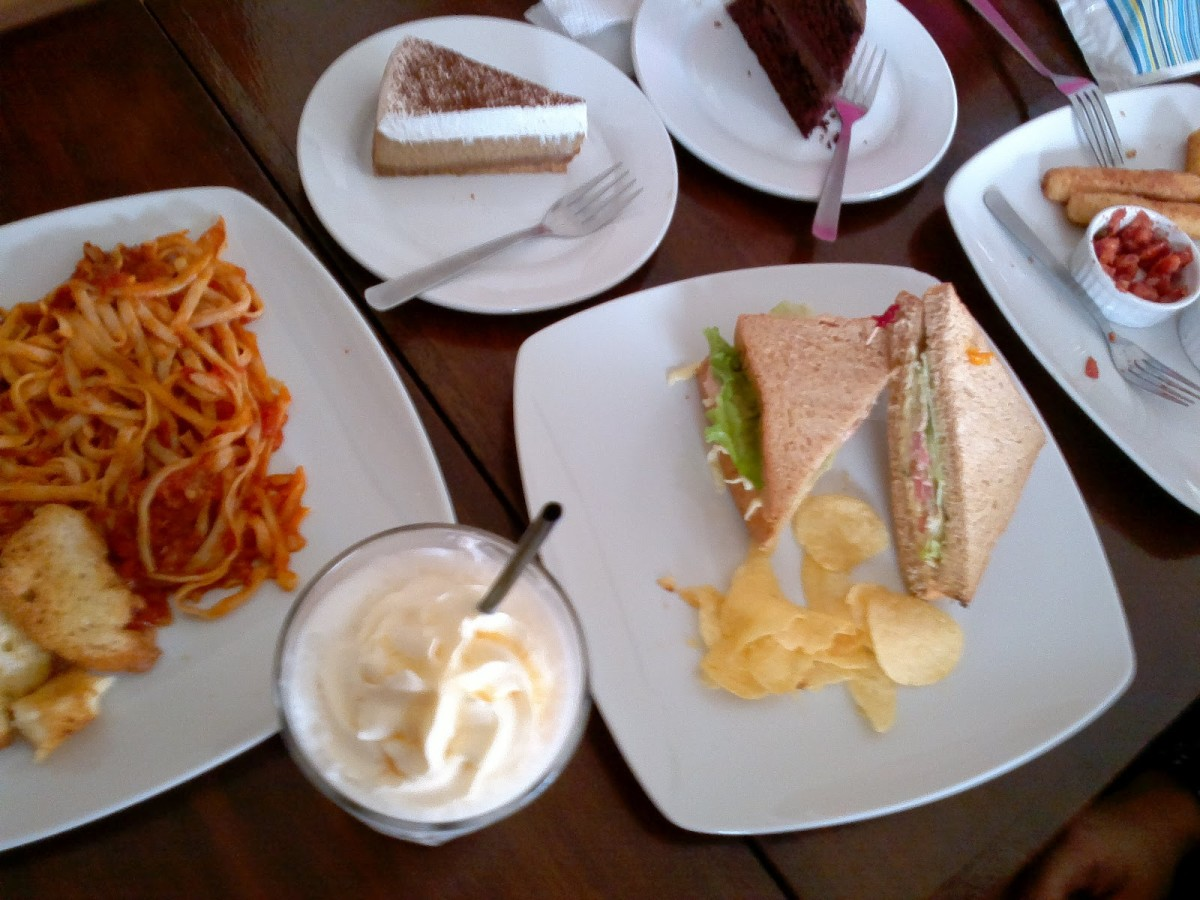 A spread of food at Cafe Cristina -- clockwise: cappuccino cheesecake, chocolate cake, tuna and crab sandwich, chocolate milkshake, and tuna and tomato pasta,