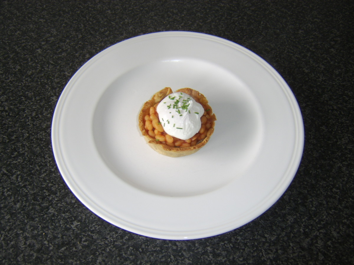A reheated Scotch pie is topped with heated baked beans in tomato sauce and a freshly poached egg