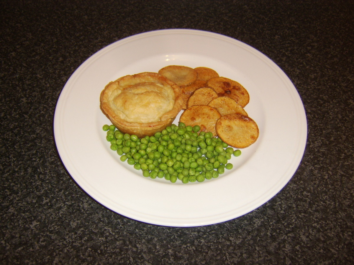 Beef puff pastry Scotch pie served with deep fried potato discs and peas