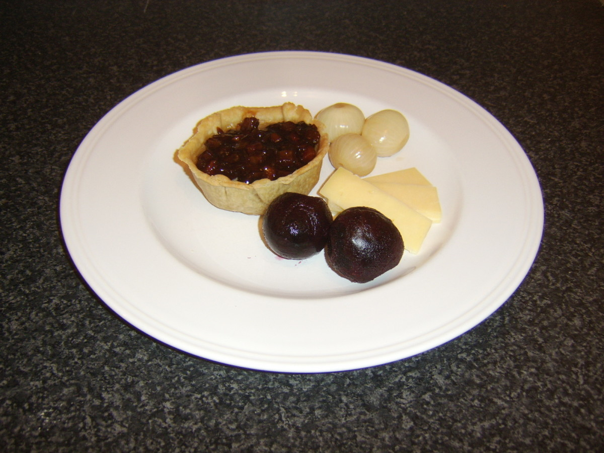 A cold Scotch Pie served with cheese and a selection of pickles