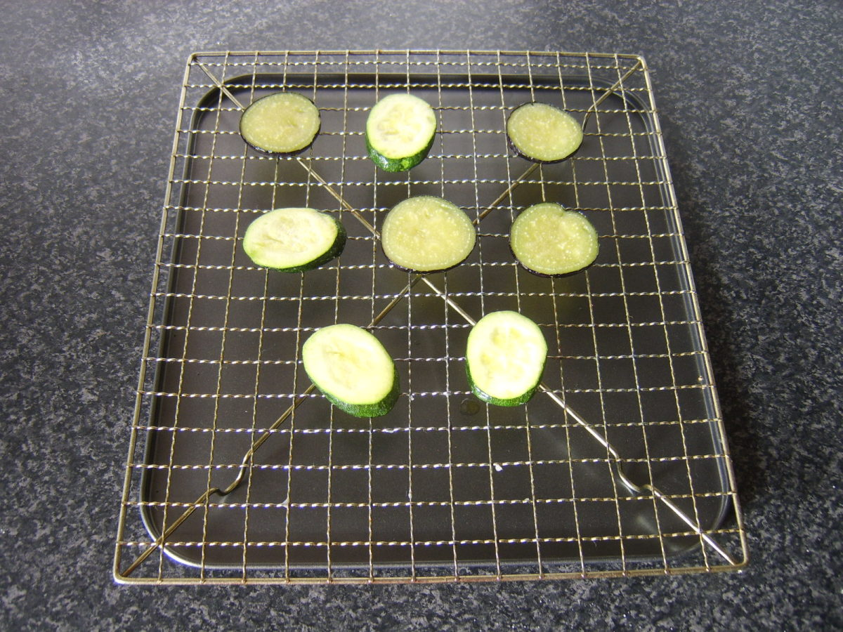 Courgette and aubergine slices are drained and rested on a wire rack