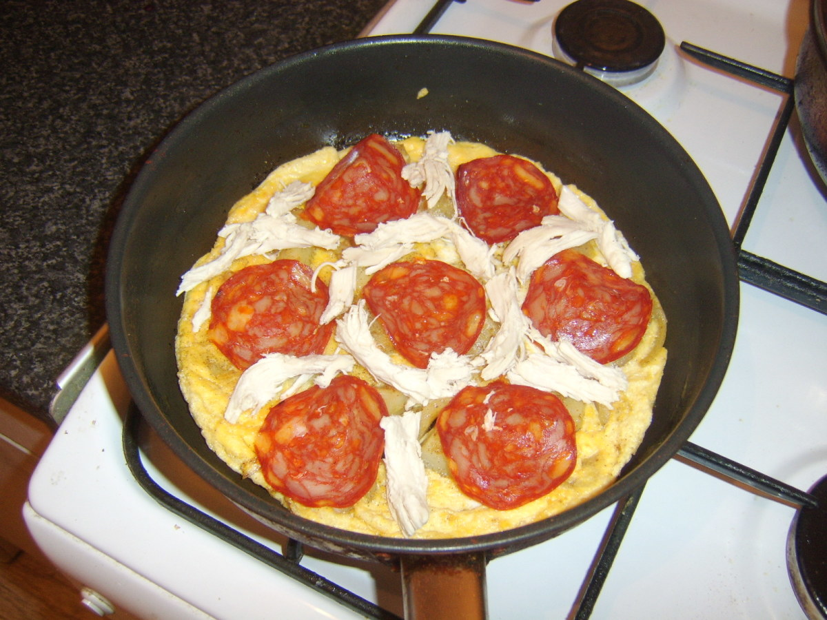 Chorizo and chicken are laid on top of the tortilla