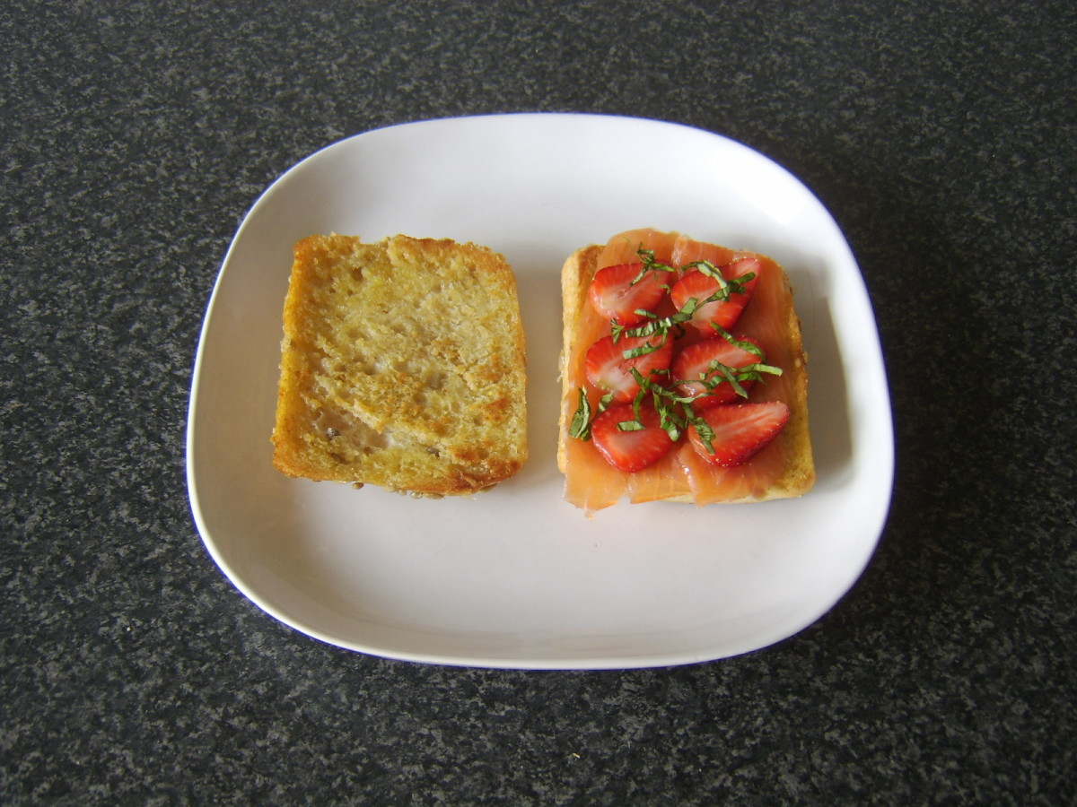 Basil is scattered over strawberries and smoked salmon