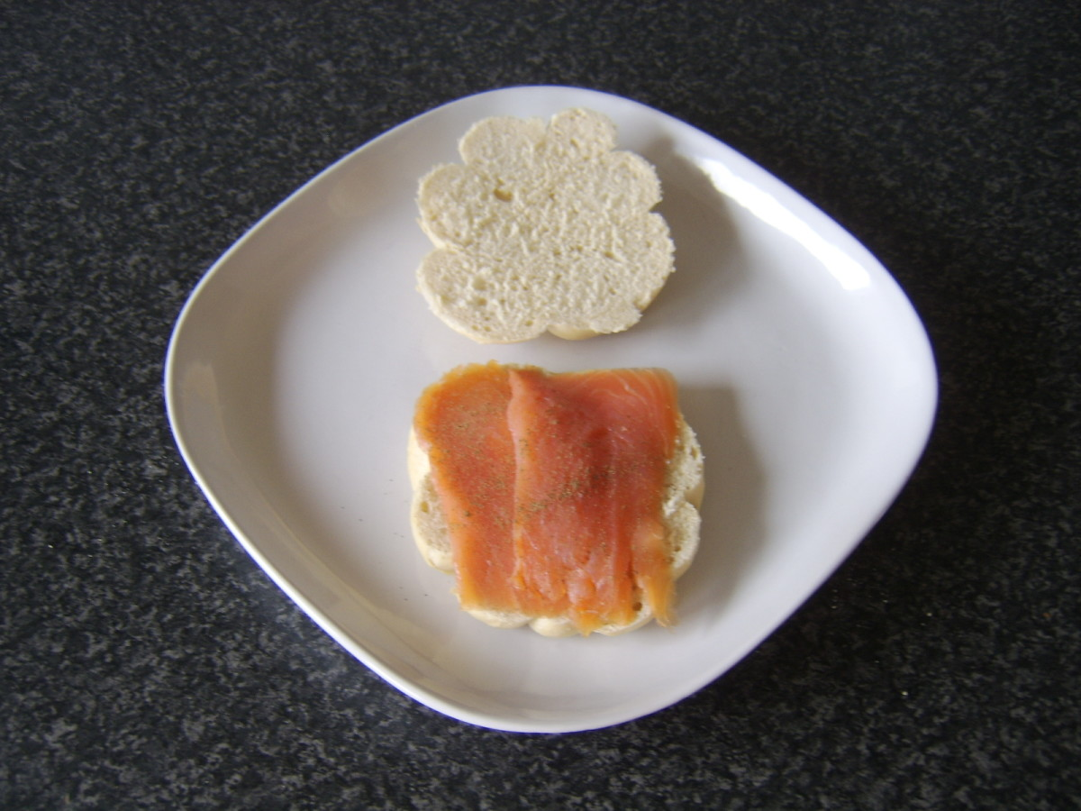 Smoked salmon is laid on half a bread roll and seasoned with lemon juice and black pepper