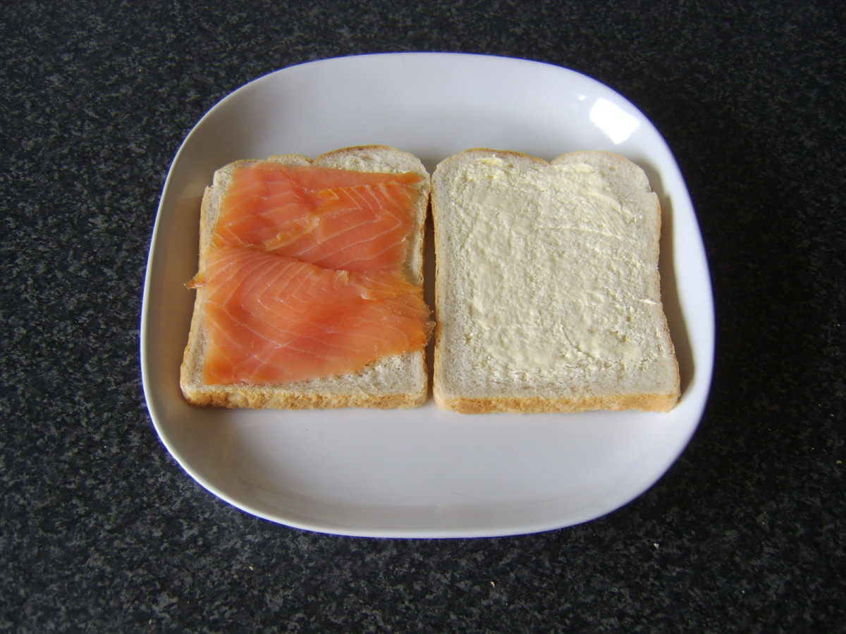 Smoked salmon is laid on one slice of the buttered bread