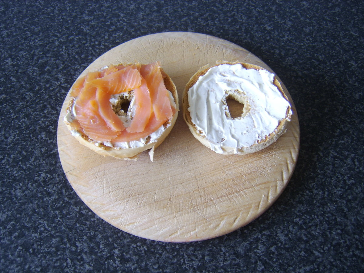 Smoked salmon is laid on one half of the bagel