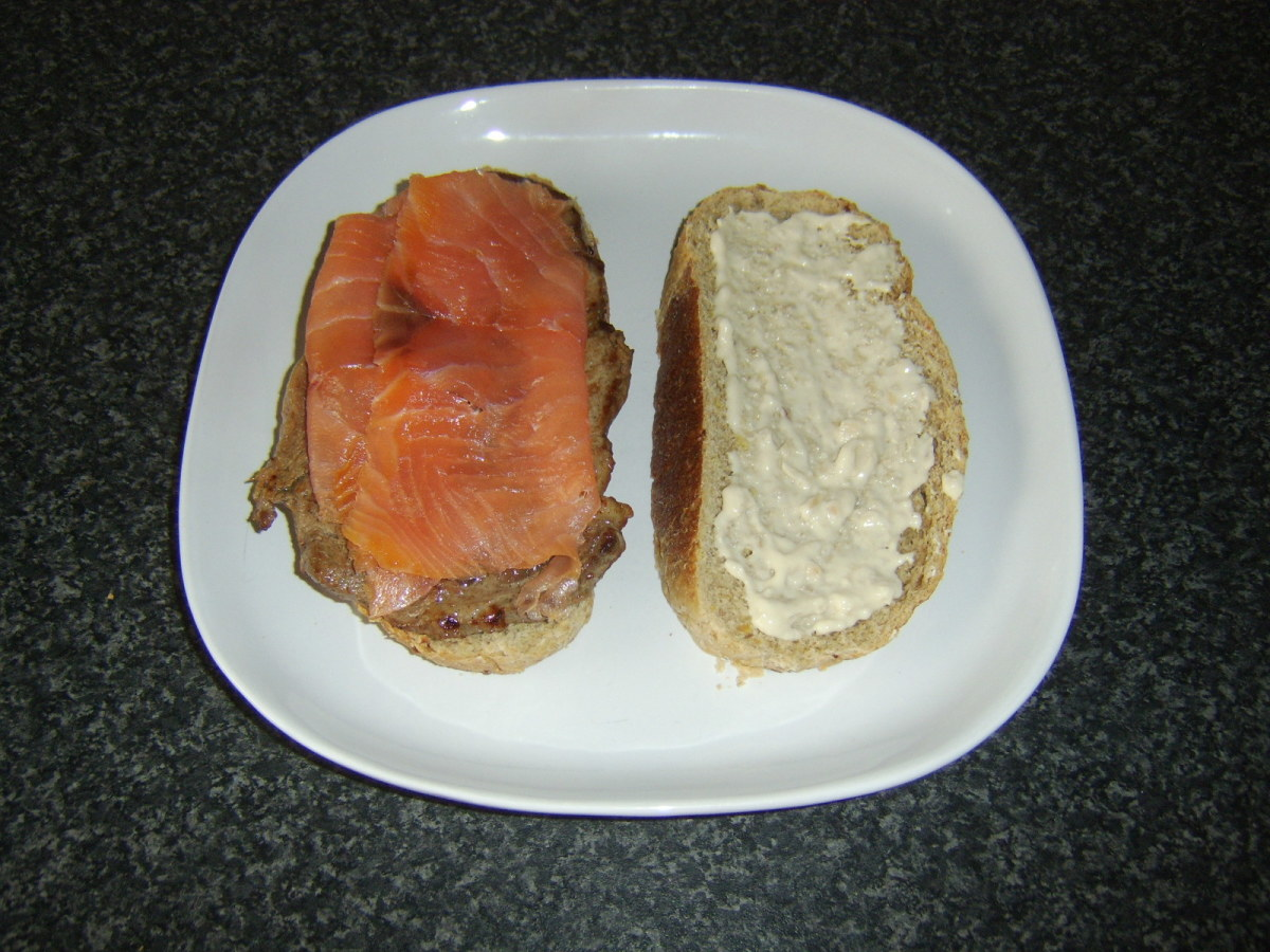 Smoked salmon slices are laid over steak