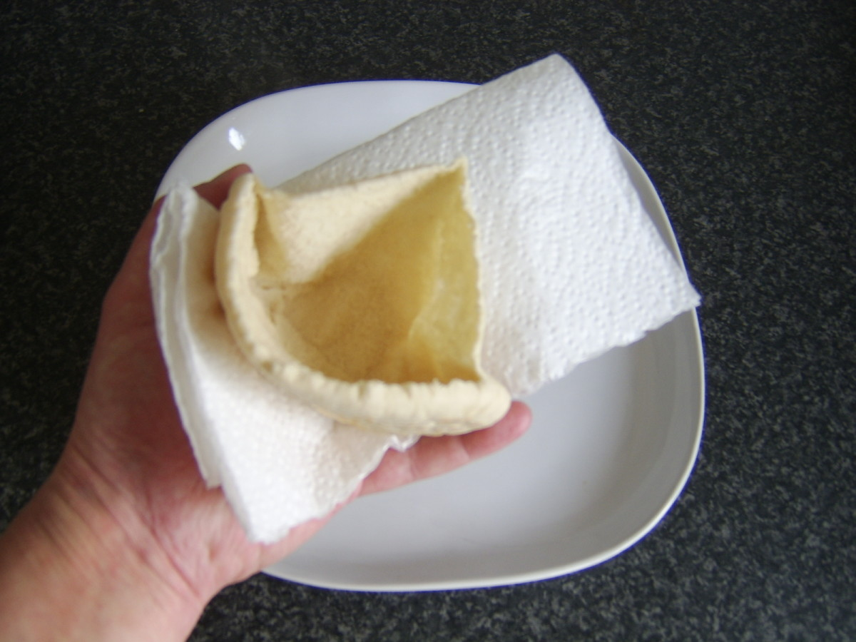 First, you must open the pitta bread in order to fill it.