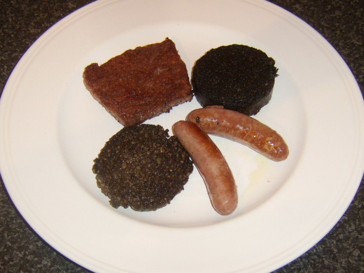 Sausages, black pudding and haggis on a heated plate