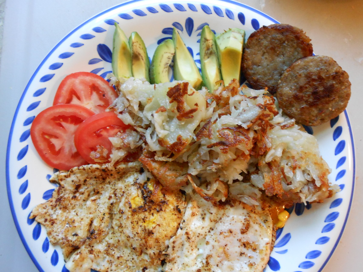 "A ""wood cutter's breakfast:""  2 eggs, hash browns, sausage served with sliced avocado and tomato."