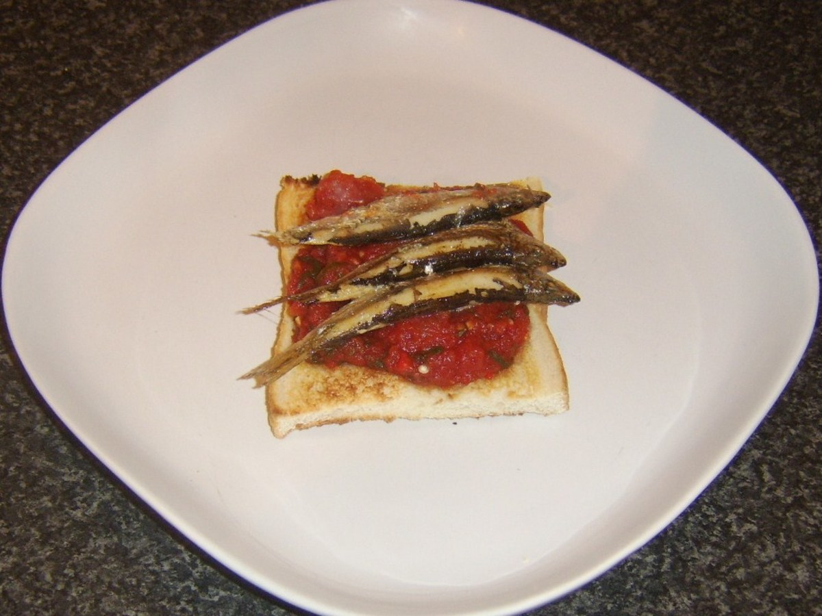 Grilled sprats are laid on spicy tomato sauce