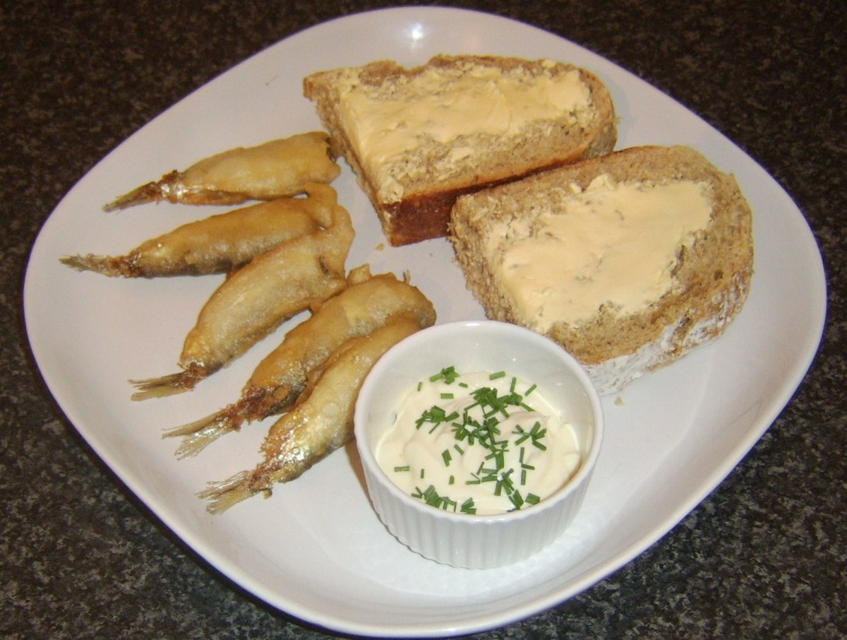 Sprats are deep fried in batter and served with a garlic and chive dip, bread and butter