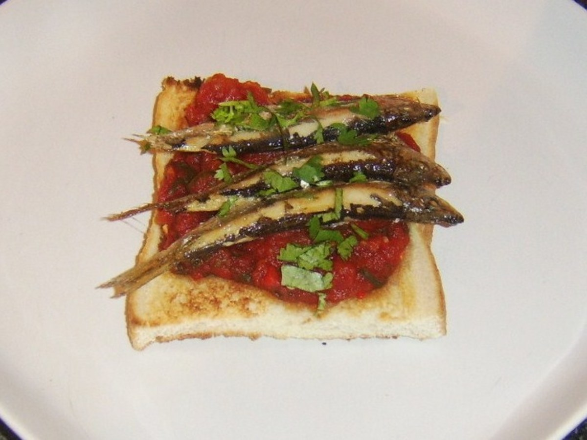 Grilled or broiled sprats served on a bed of spicy tomato sauce on toast