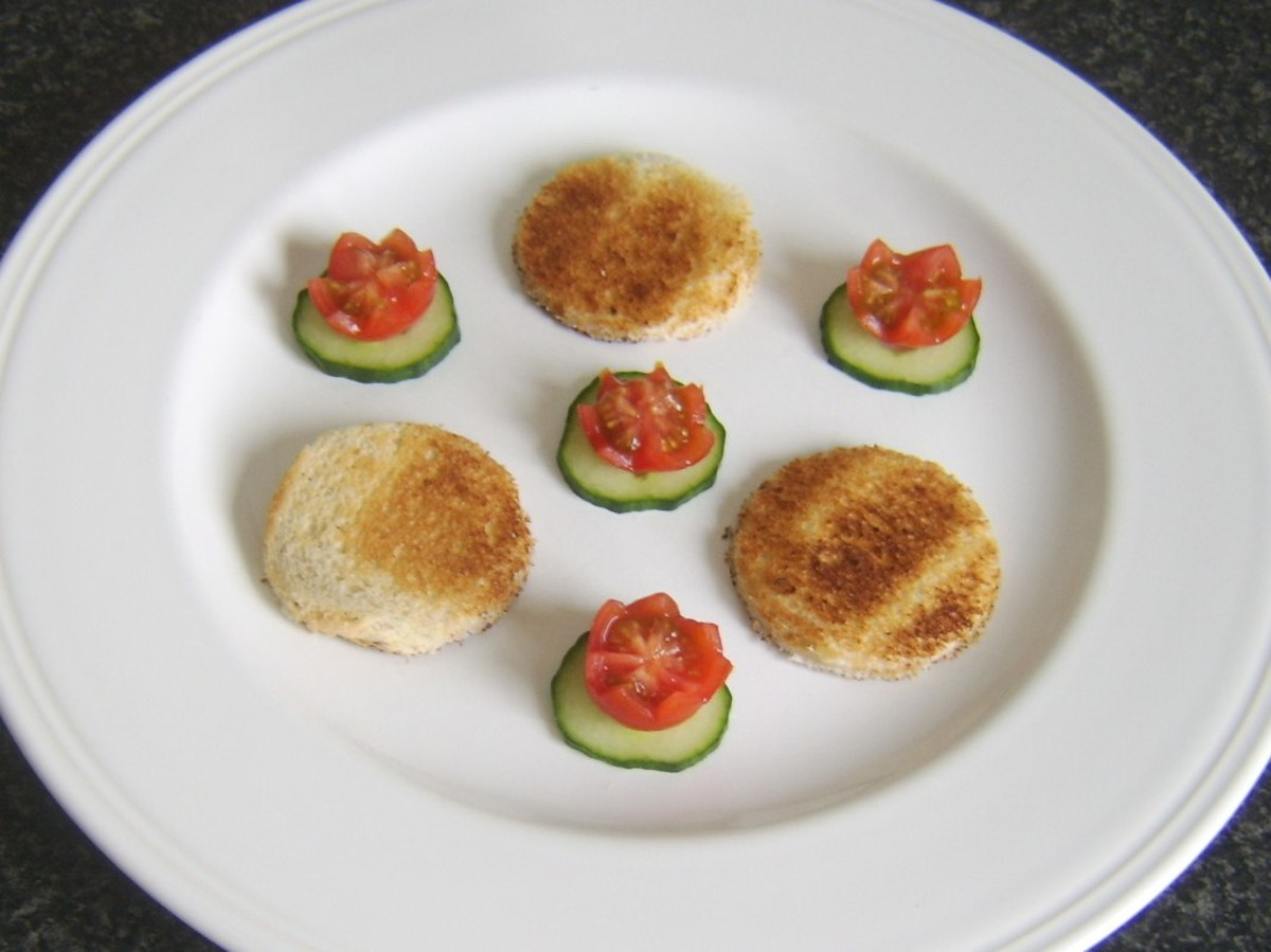 Toast circles are plated with tomato and cucumber