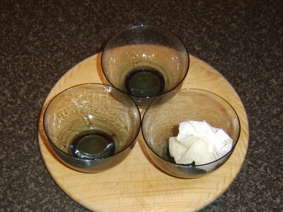 Small glass bowls are oiled for receiving cracked quail eggs